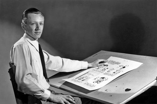 Charles Schulz en los años cuarenta, en su mesa de dibujo.